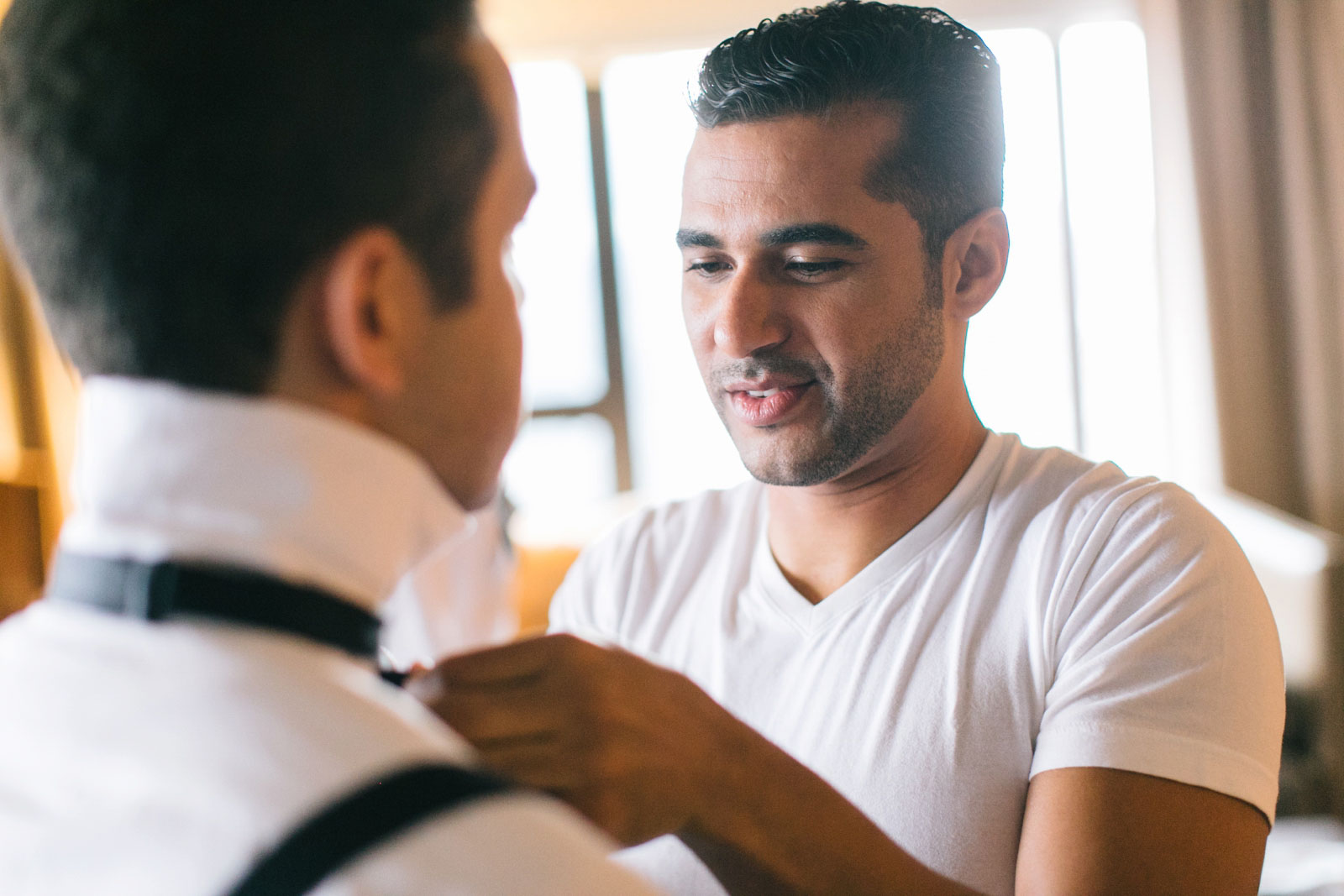 Groom helping groomsman with his bow tie in getting ready suite with lots of natural light