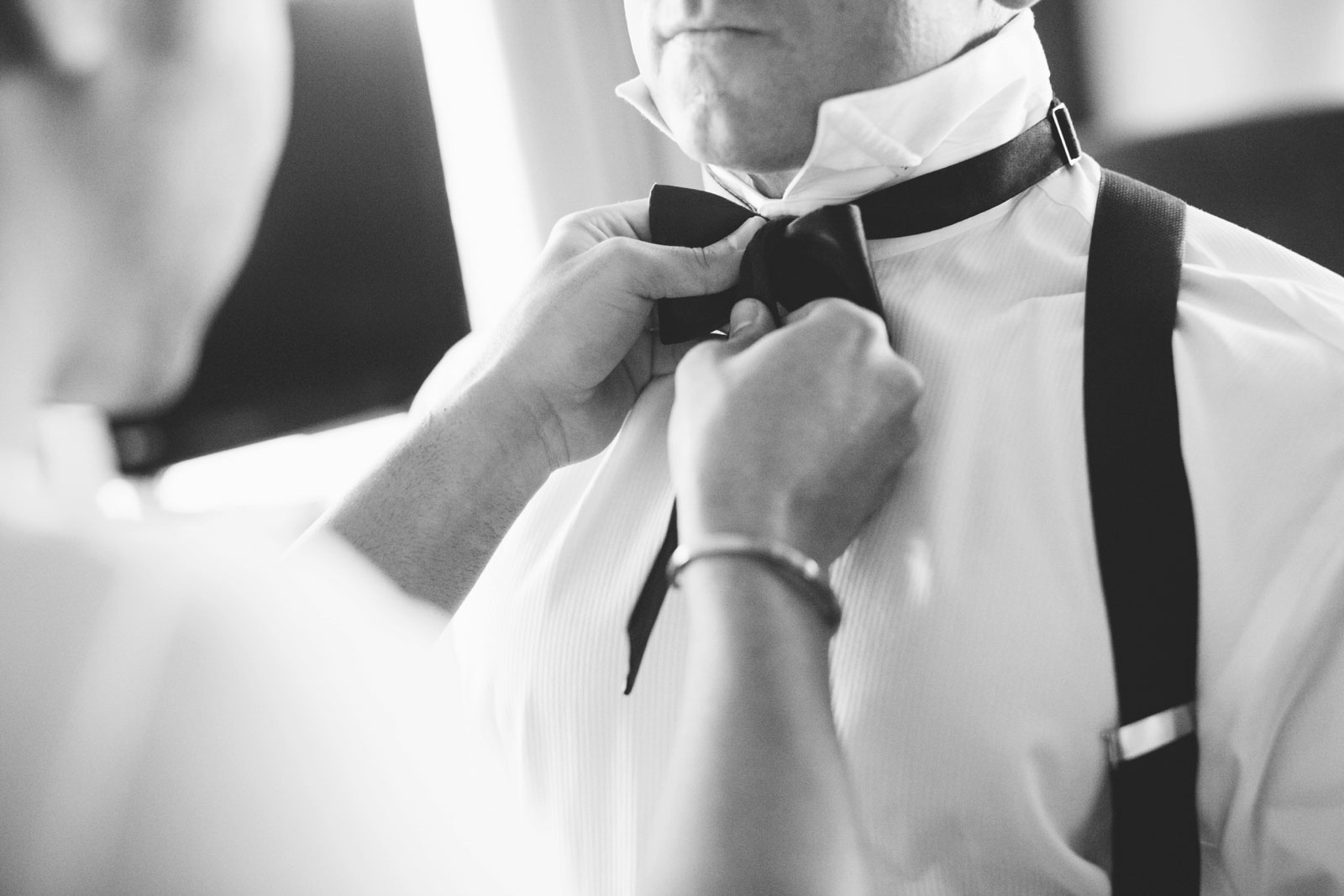 Black and white shot of groom helping groomsman with his bow tie in getting ready suite
