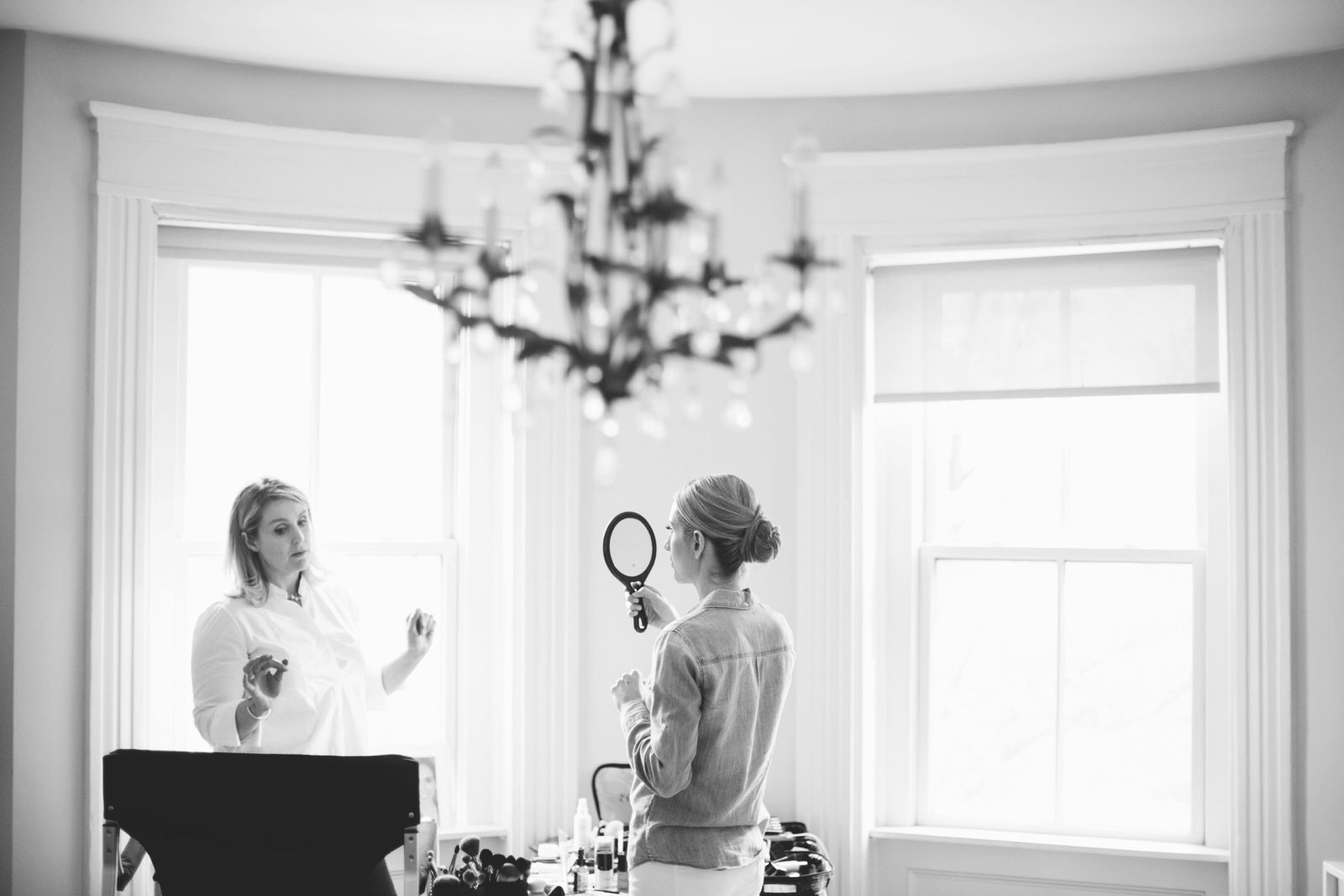 Poetic Black and white shot of bride checking her make up in hand mirror in soft natural light