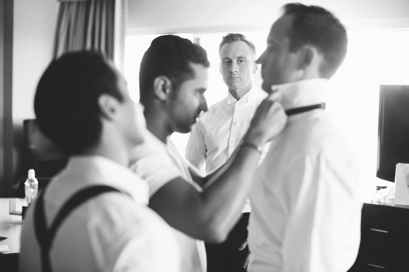 Groomsmen helping each other with their bow ties in getting ready suite, groom getting ready