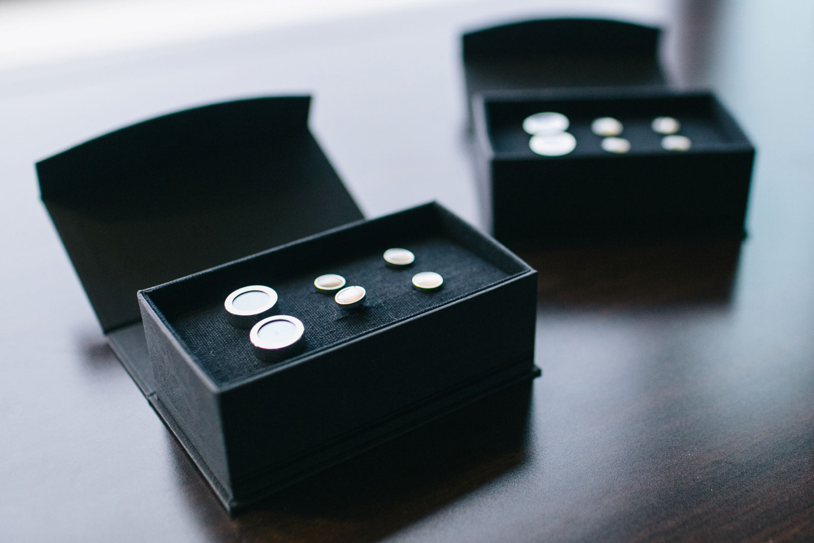Detail shot of the groom's cufflinks in a black presentation box on the windowsill