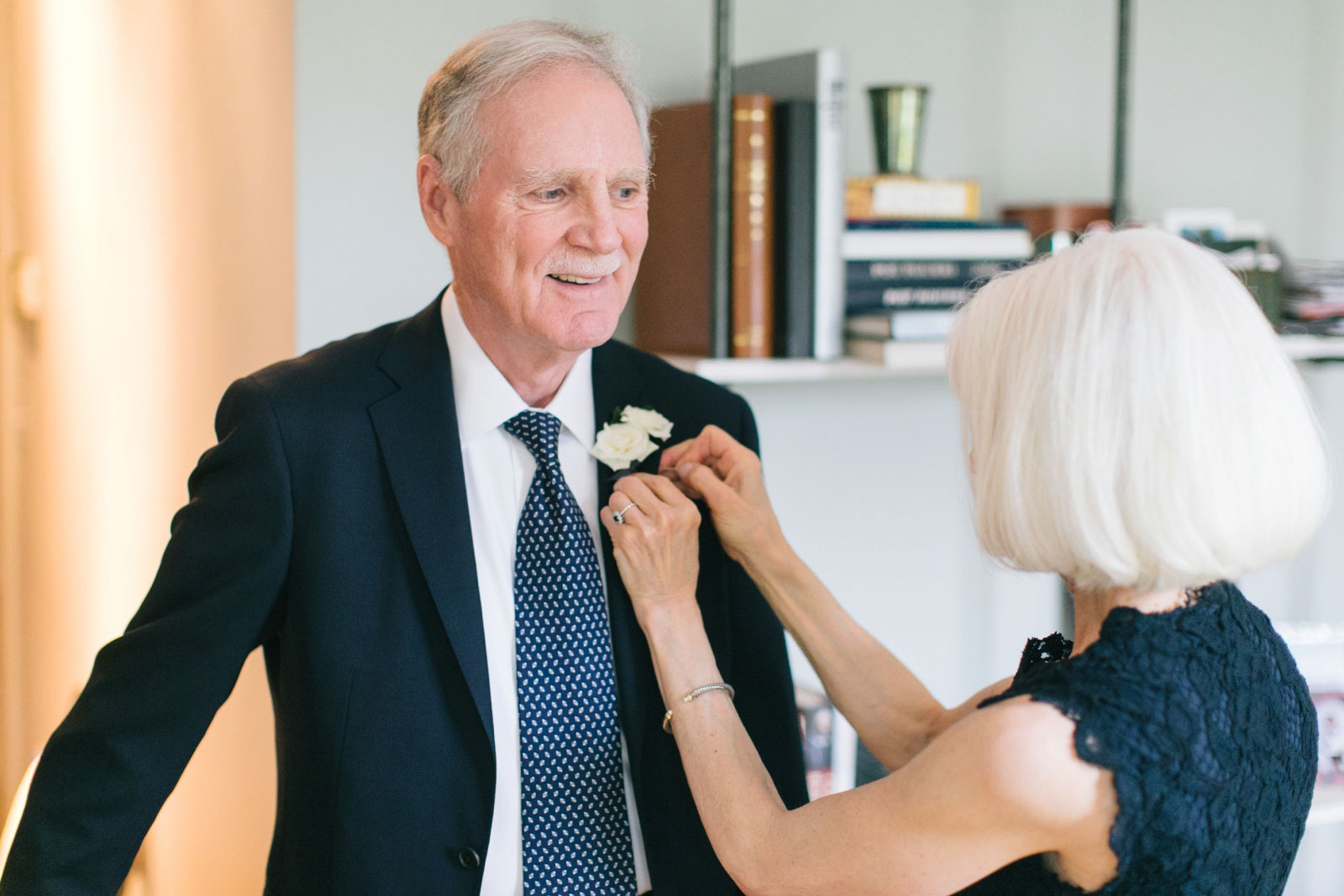 mother of the bride helps father of the bride with his white rose boutonniere while getting ready