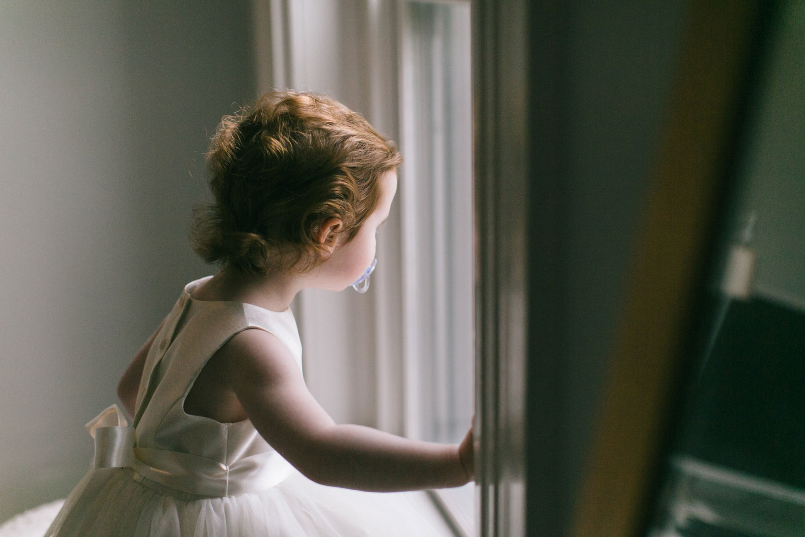 candid of flower girl looking out the window, getting ready photos with natural light