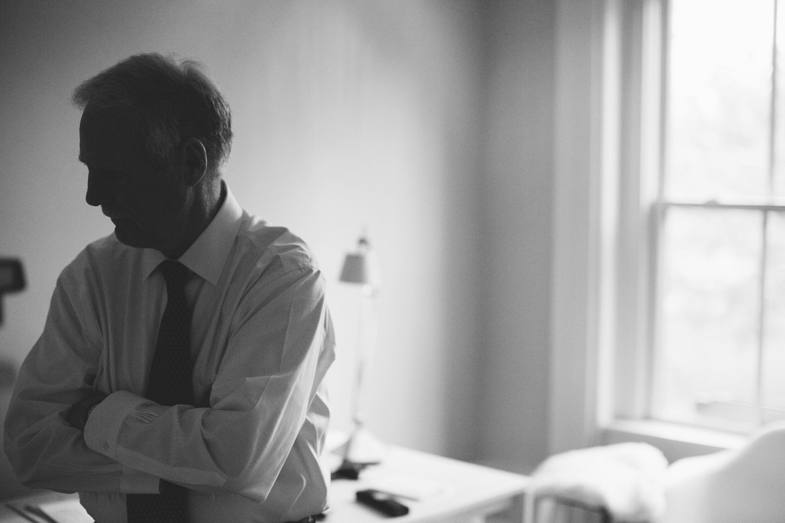 moody black and white silhouette of father of the bride getting ready in back bay apartment