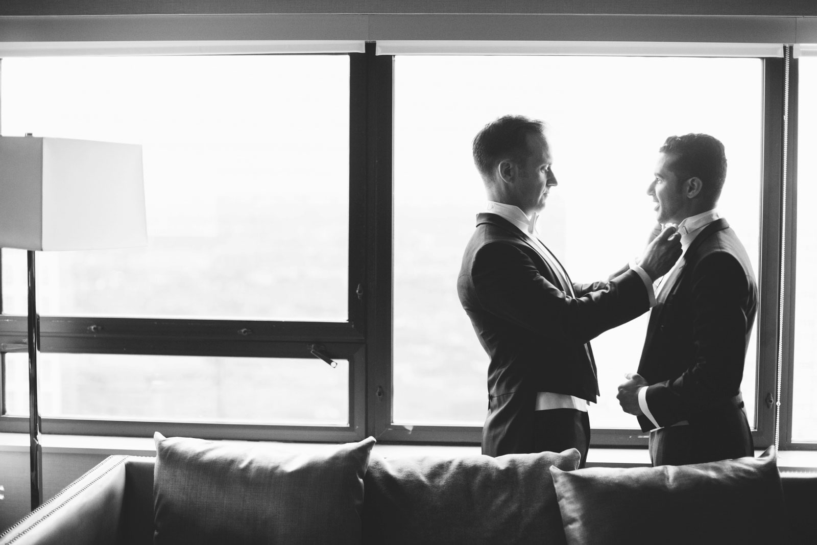 Black and white shot of grooms helping each other with their bow ties in front of the window
