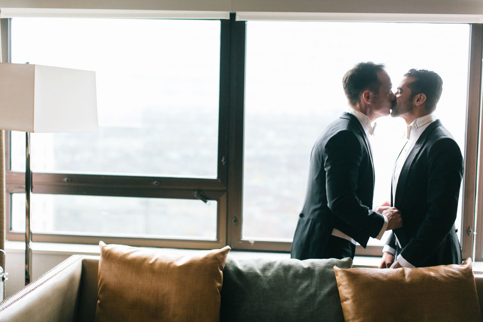 Grooms share a kiss in front of window in getting ready suite before the ceremony