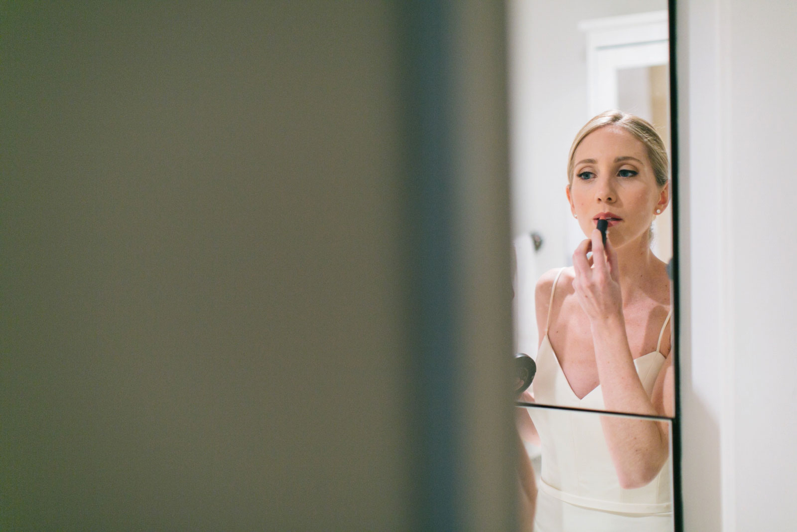peaking around corner at bride putting lipstick on in mirror while getting ready at her apartment