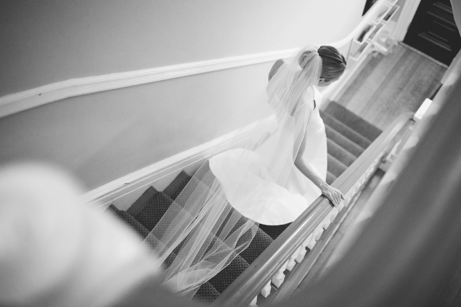 black and white shot of bride walking down stairs of her back bay apartment with veil trailing