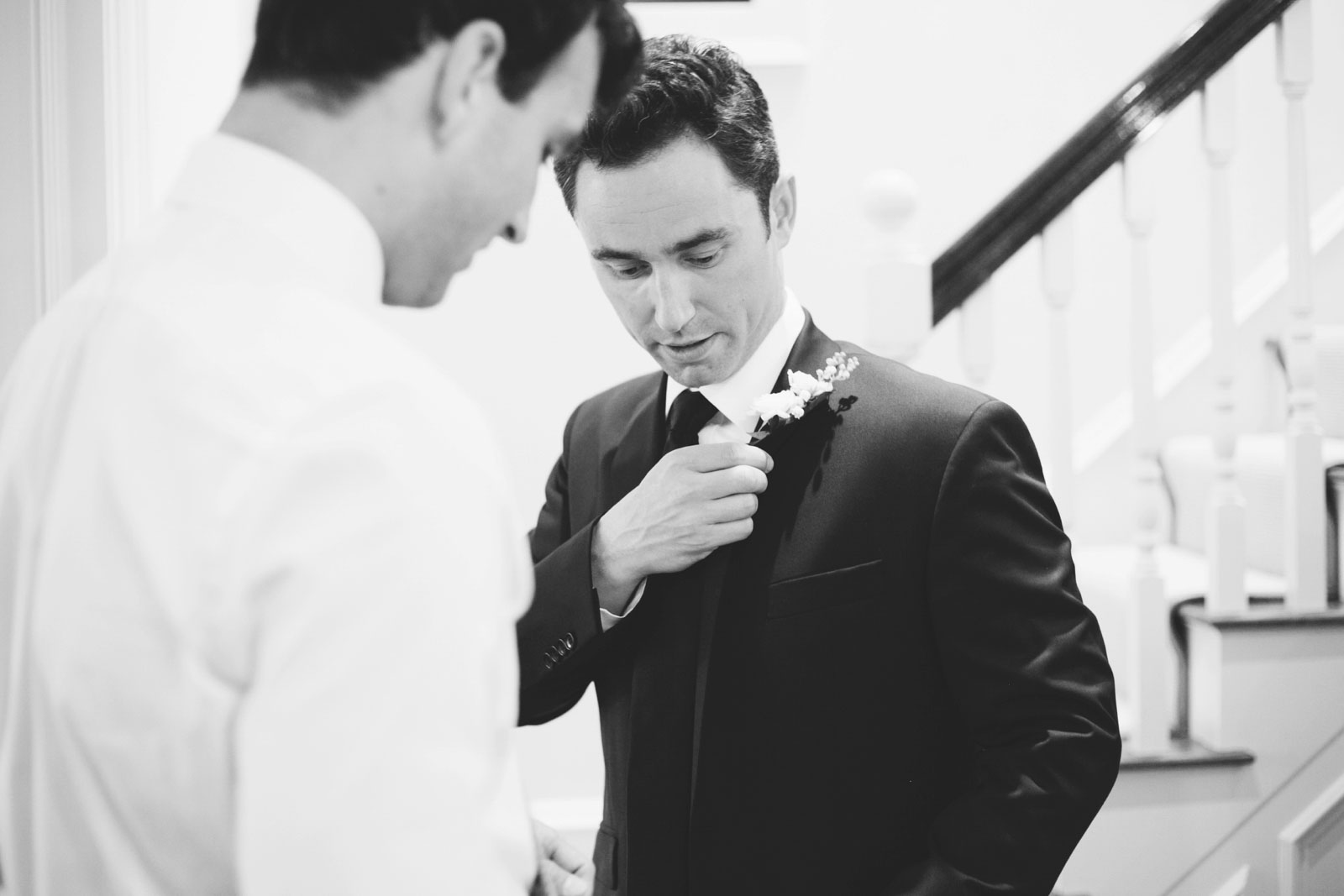 black and white shot of groom putting on his boutonniere while getting ready at home in Back Bay