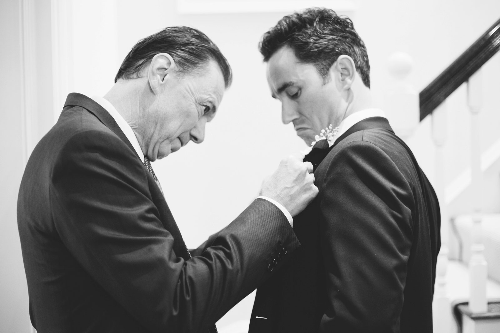 black and white shot of father of groom helping groom with boutonniere while getting ready at home
