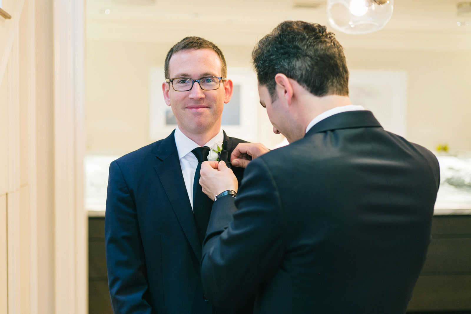 groomsmen putting on boutonnieres while getting ready before Boston Public Library wedding
