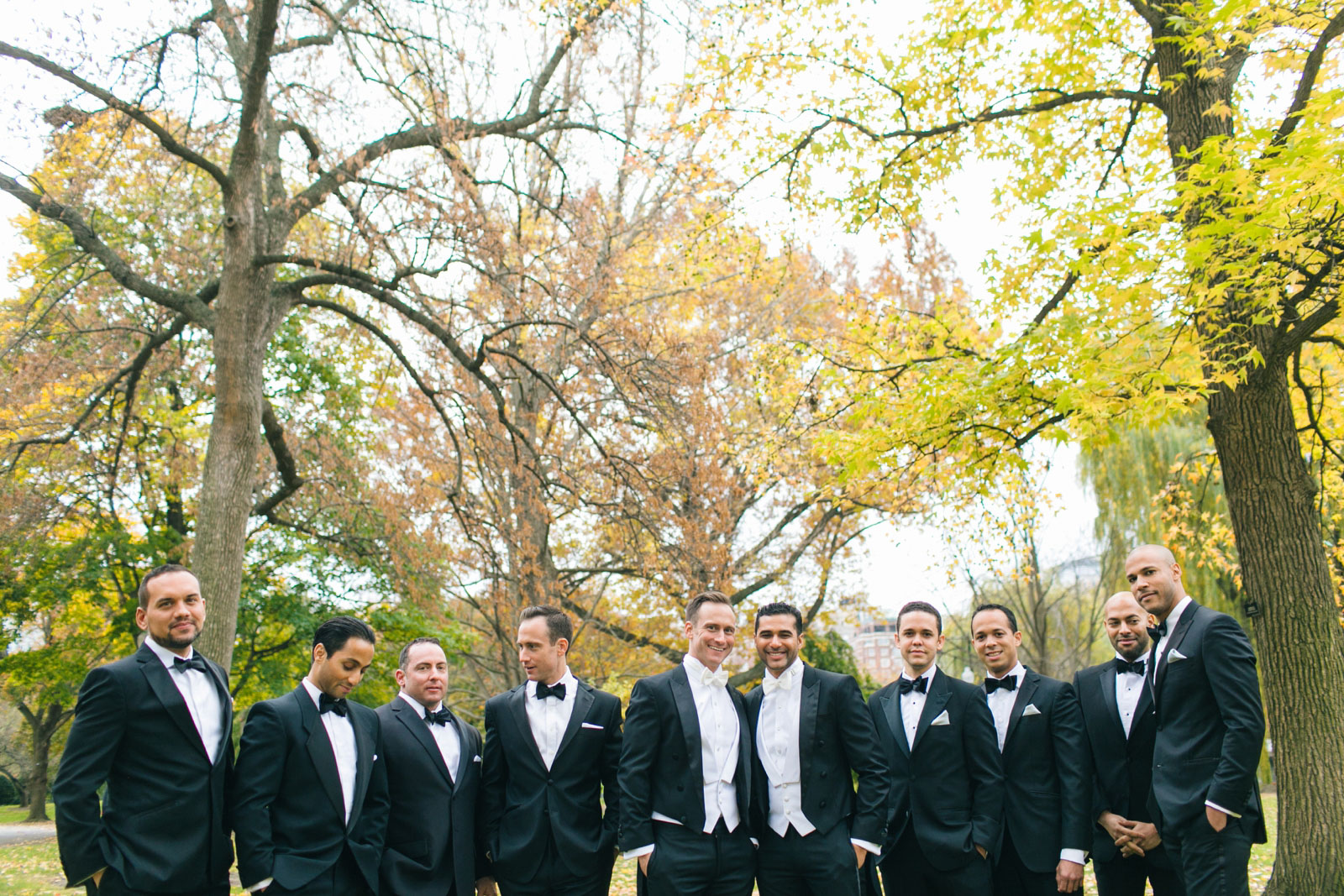 Candid groomsmen portrait standing under tree with bright fall foliage in Boston public gardens