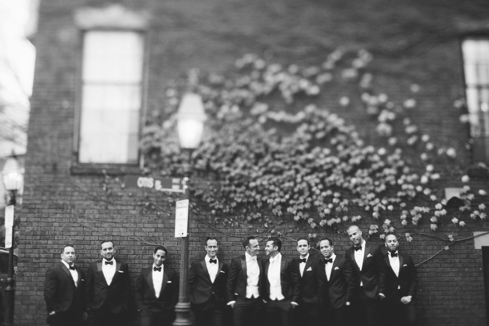 Black and white black-tie groomsmen portrait in front of brick wall with ivy in Boston's back bay