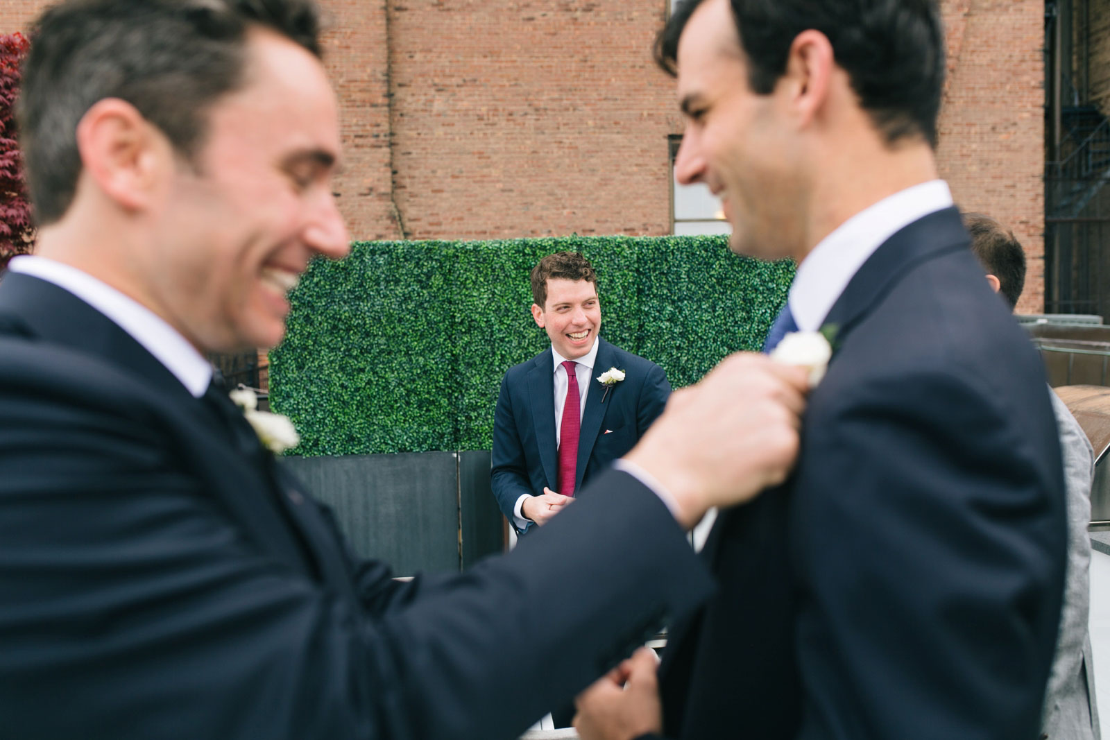 candids of Groomsmen hanging out on roof deck while getting ready in back bay condo in Boston