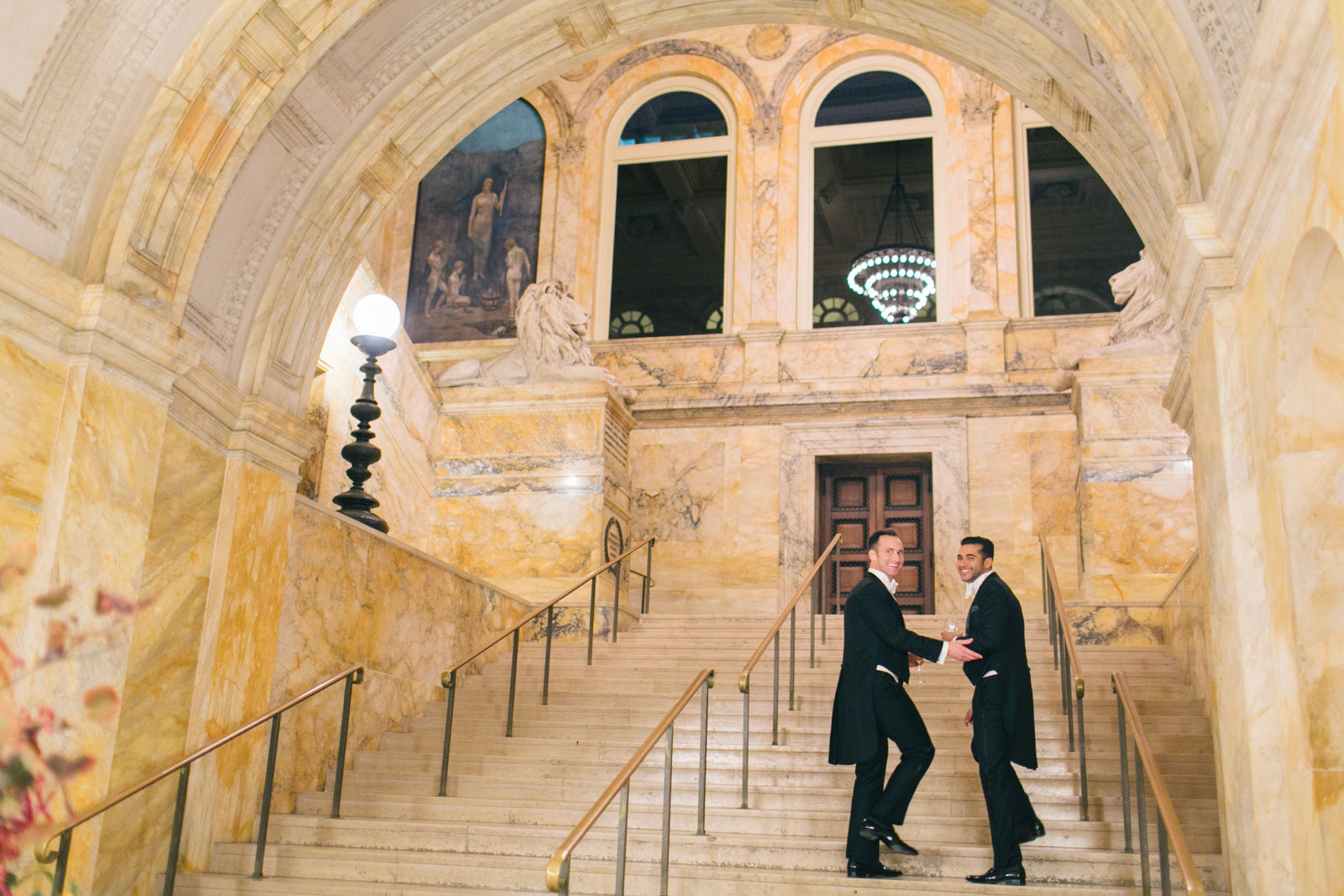 Grooms walking up elegant marble stairs at quinetessential entryway to Boston public library