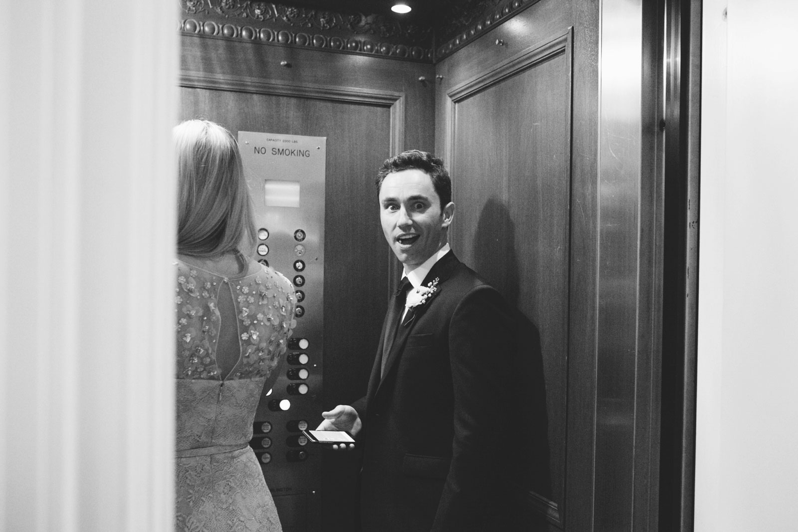 silly shot of groom taking elevator down at apartment in Back Bay in black and white