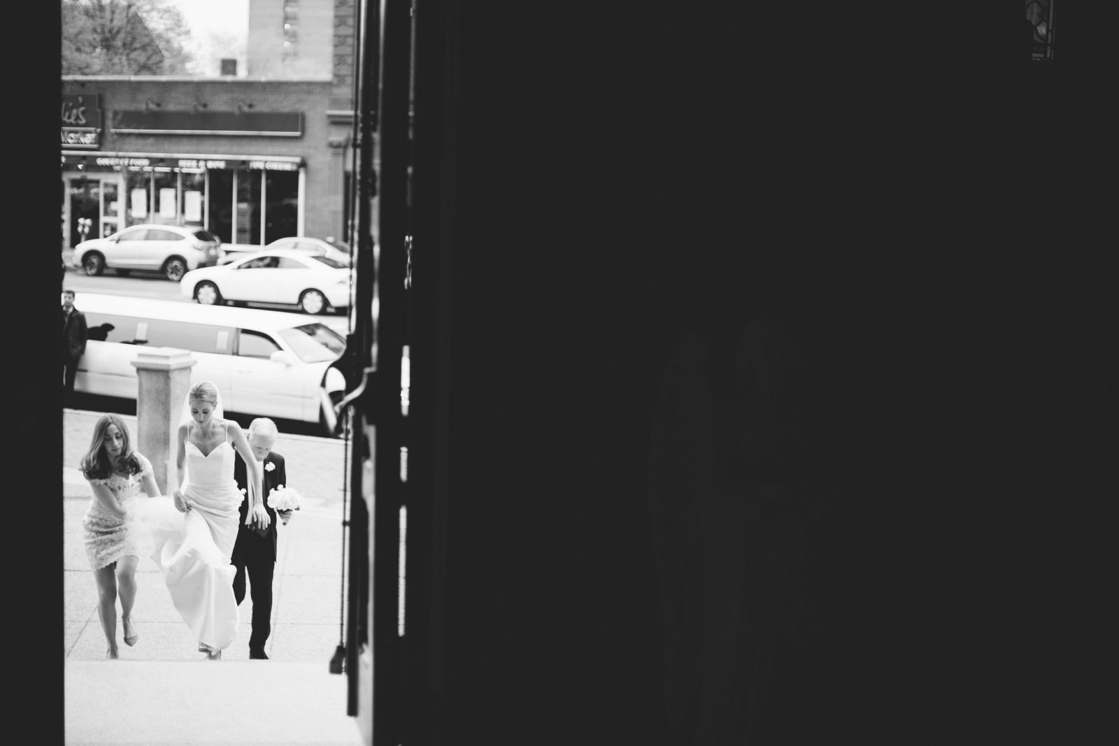 black and white shot looking through door at bride walking up steps of church