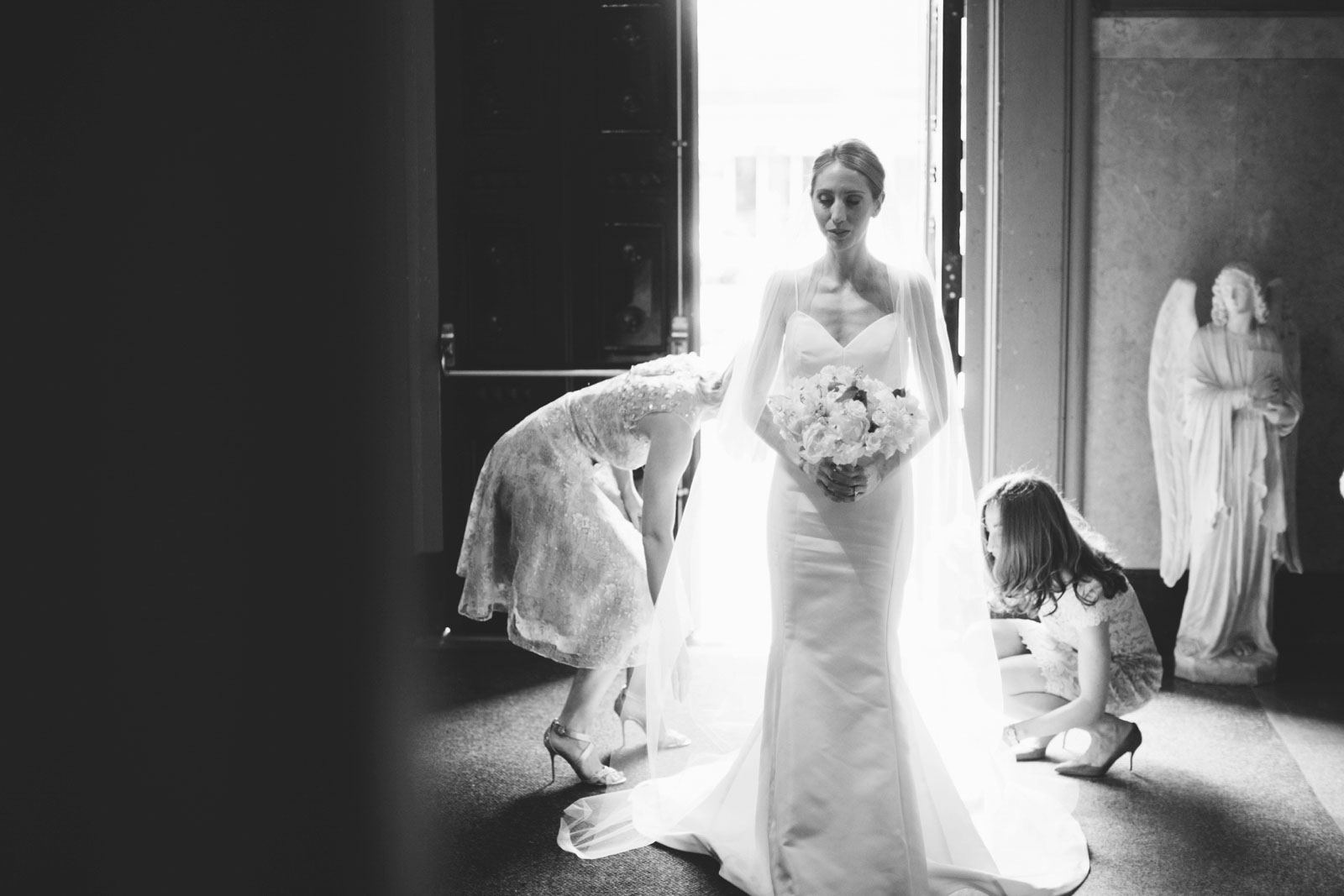 bridesmaids help fix bride's train in entryway of church with beautiful natural light behind her