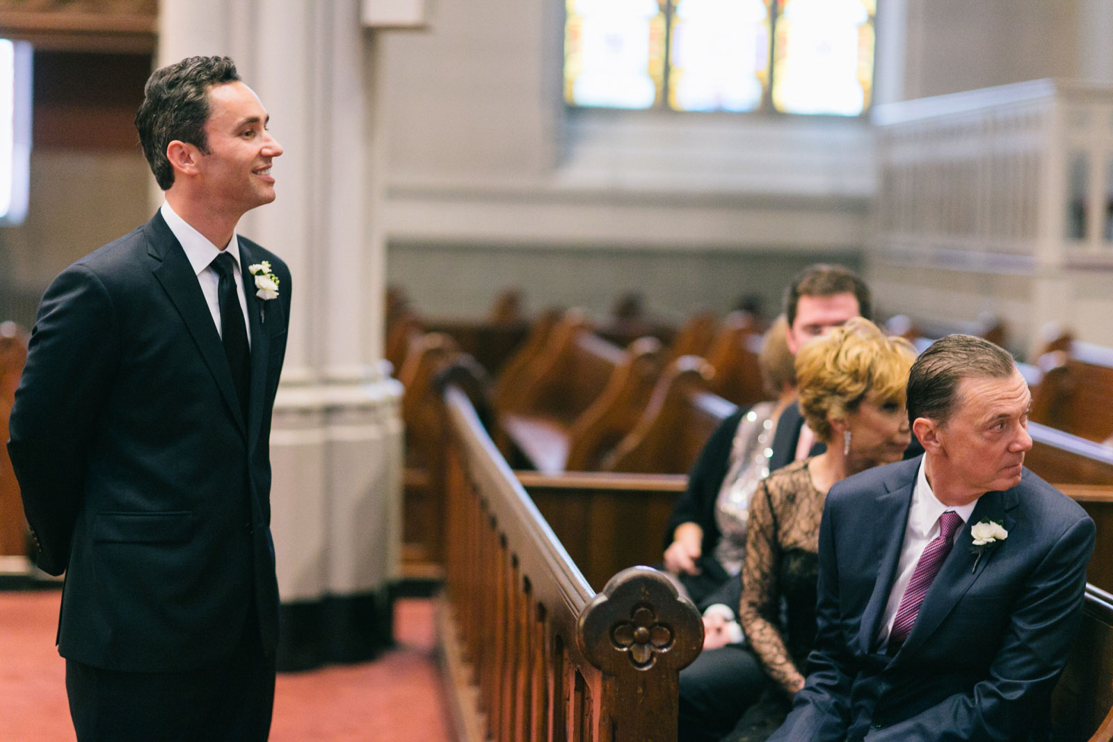 groom smiling at bride as bride walks down the aisle at church in South end in Boston