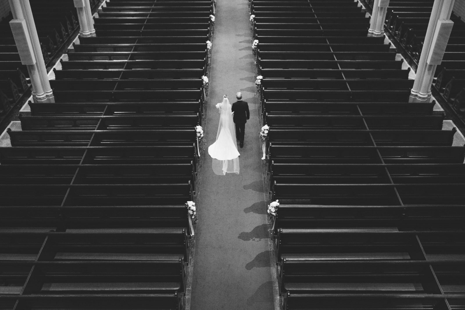 black and white shot from balcony of bride walking down aisle at Cathedral of the Holy Cross