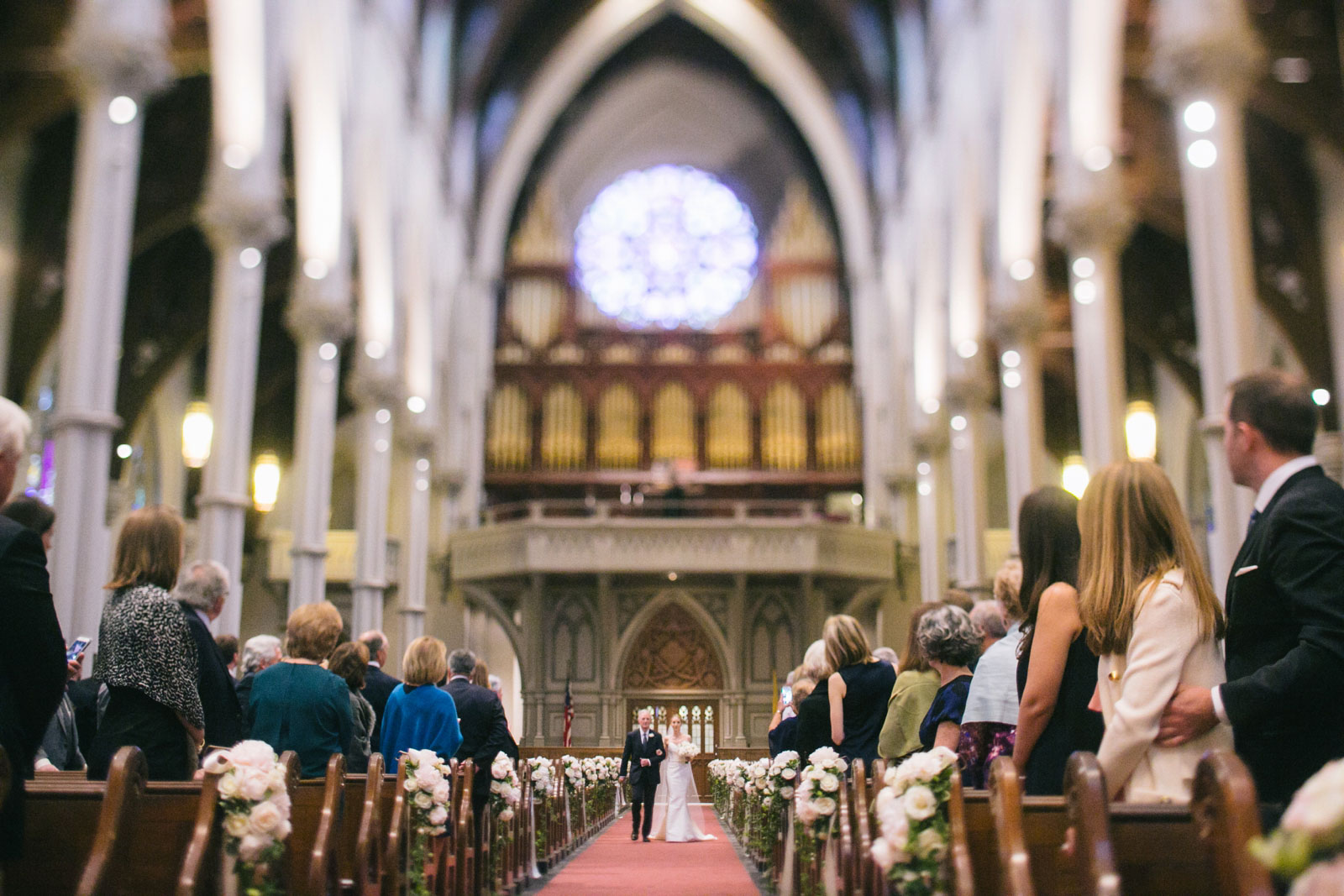 bride walking down aisle of giant cathedral in south end with pillars and stained glass