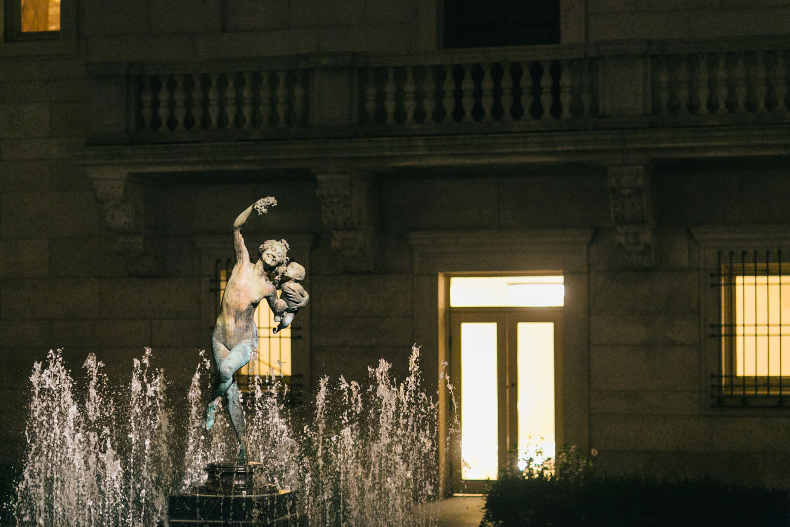 Famous statue in fountain of courtyard at Boston public library lit up at night for wedding ceremony