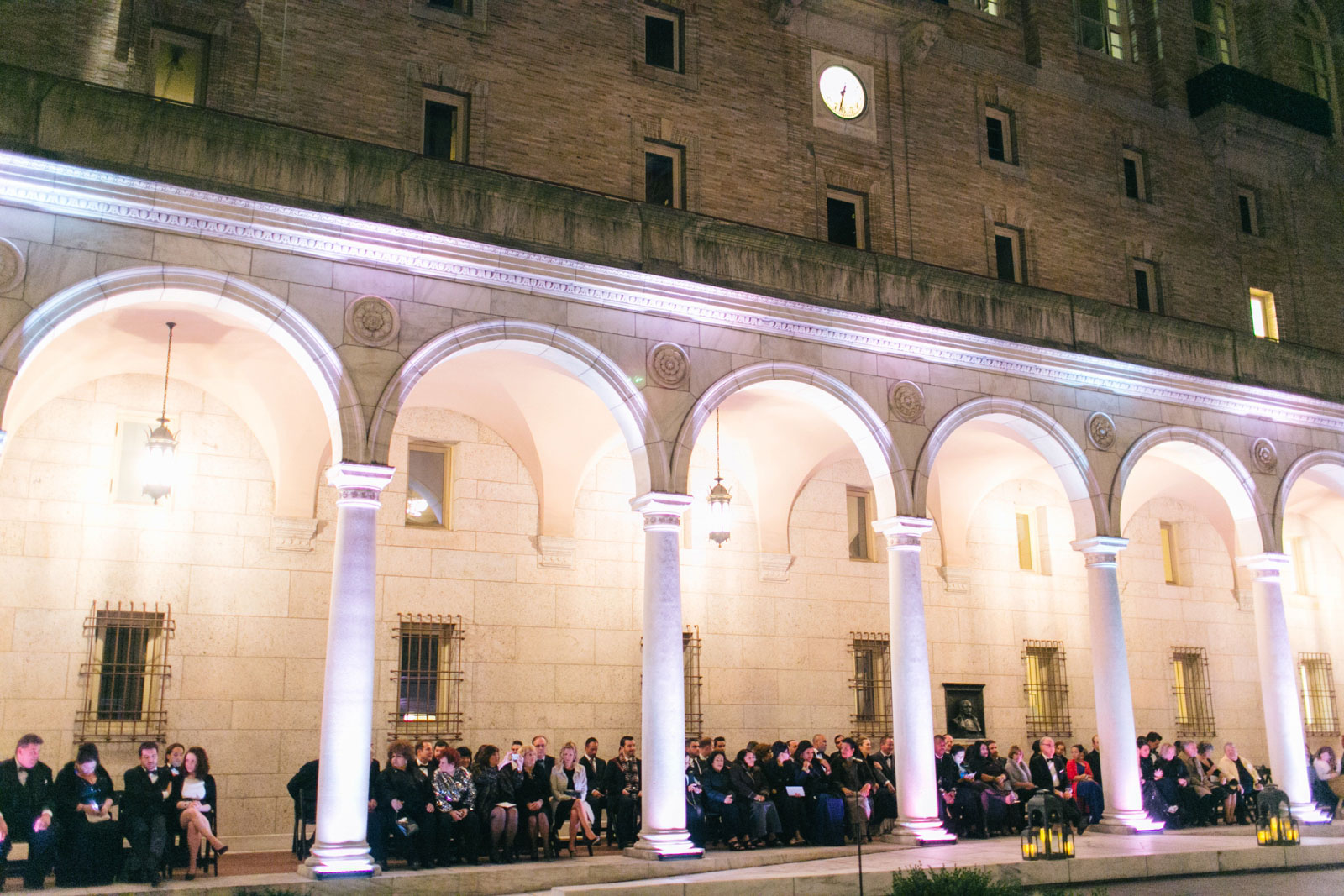 Outdoor wedding ceremony at Boston public library at night with pillars and stone architecture