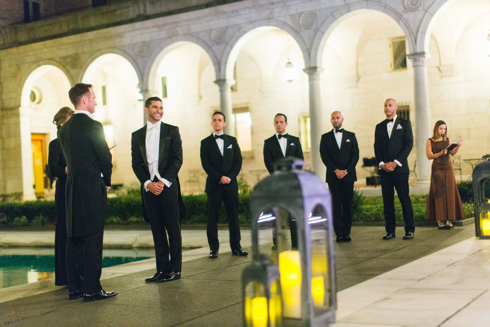 Groom looks excitedly at guests during outdoor wedding ceremony at Boston public library at night