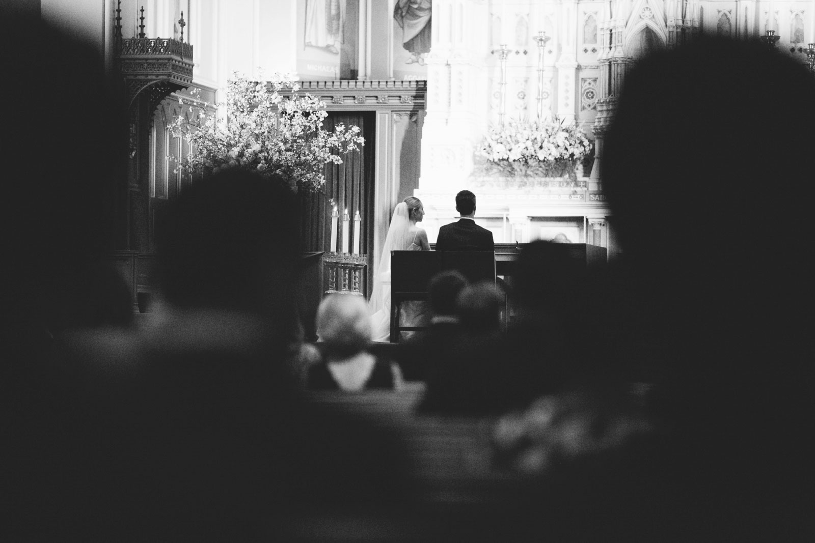 black and white shot looking through crowd at bride and groom sitting at altar during church wedding