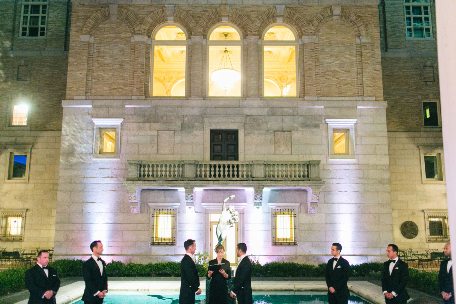 wedding ceremony in front of famous statue in courtyard of Boston public library at night