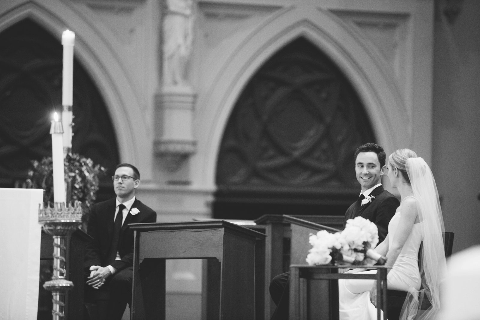 black and white shot of groom smiling at bride while they sit at altar during Roman Catholic wedding