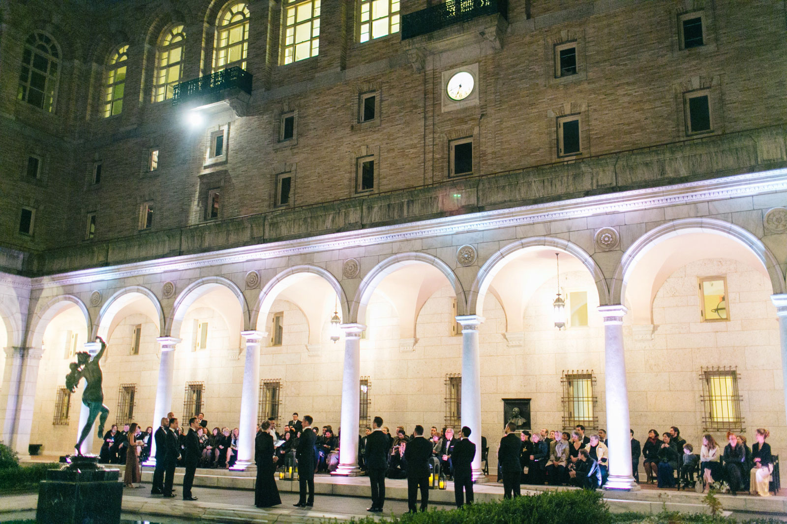 wedding ceremony in courtyard of Boston public library at night with Roman pillars