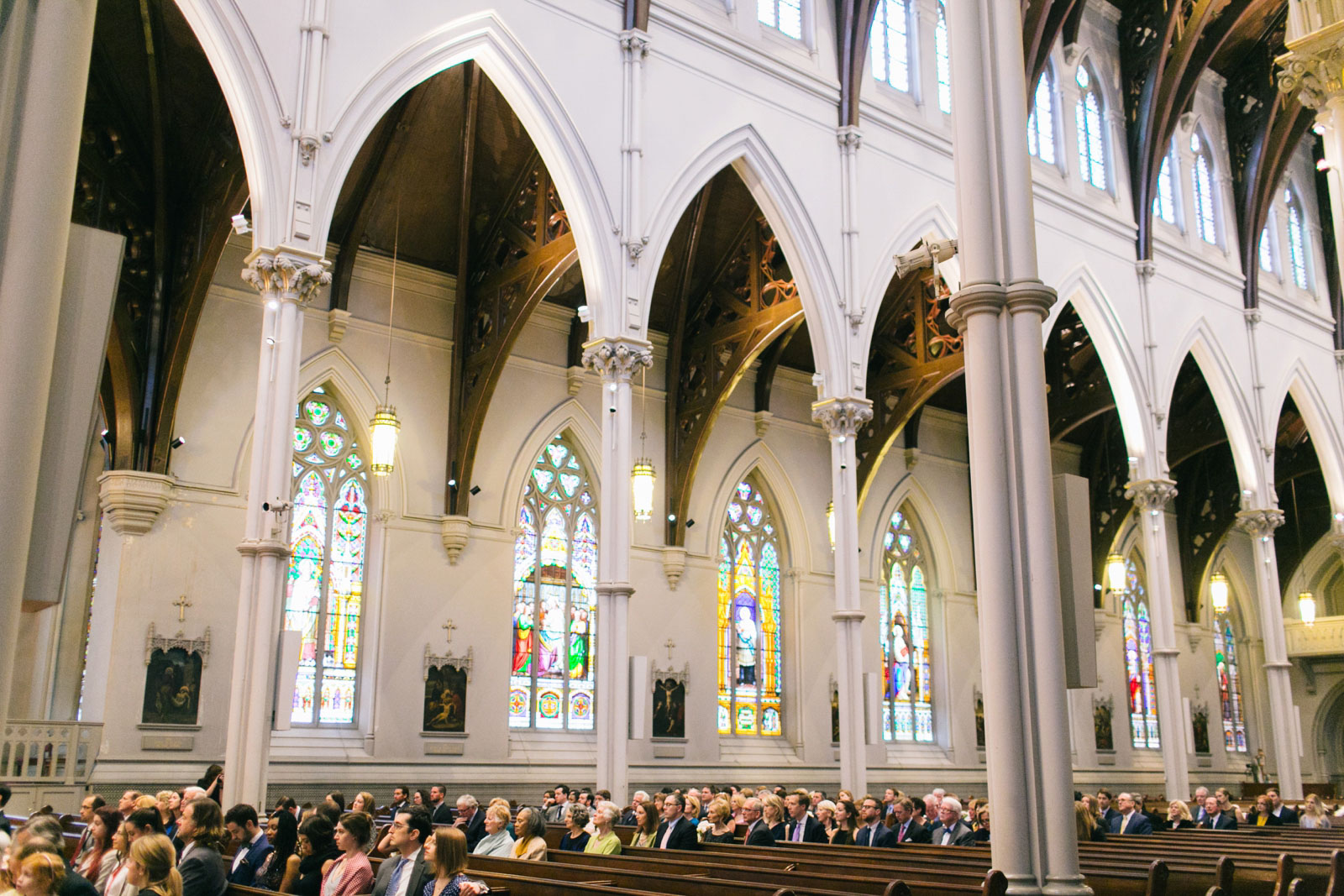 wide shot of wedding guests watching ceremony in cathedral with carved pillars and stained glass