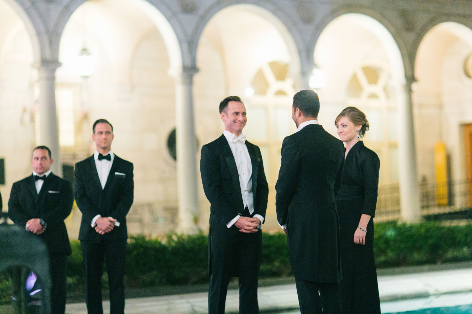 Couple smiles at each other during nighttime outdoor wedding ceremony at Boston public library