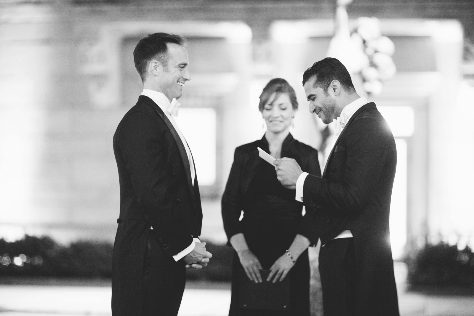 Intimate Black and white shot of groom saying his vows while other groom smiles lovingly