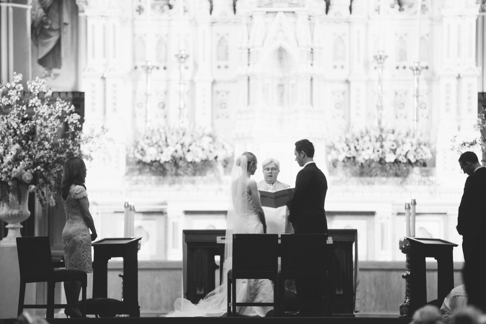 black and white silhouette of bride and groom standing at altar at church ceremony