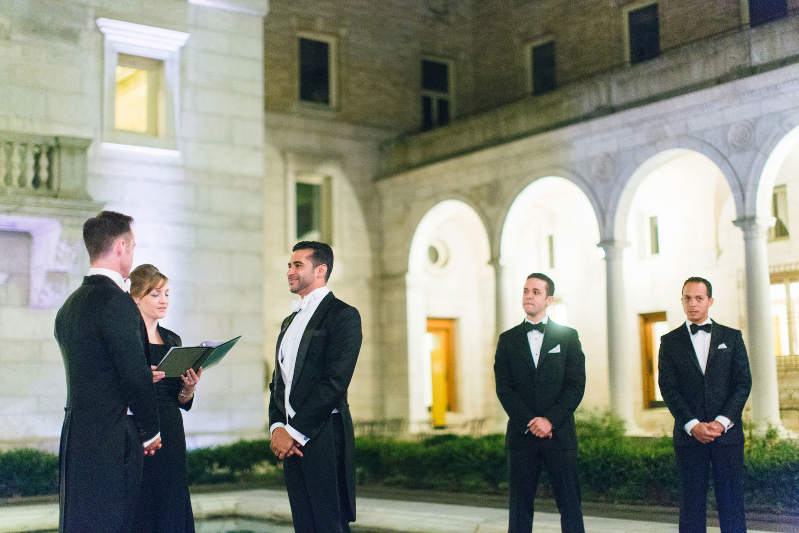 Same-sex wedding ceremony in courtyard of Boston public library at night with Roman pillars