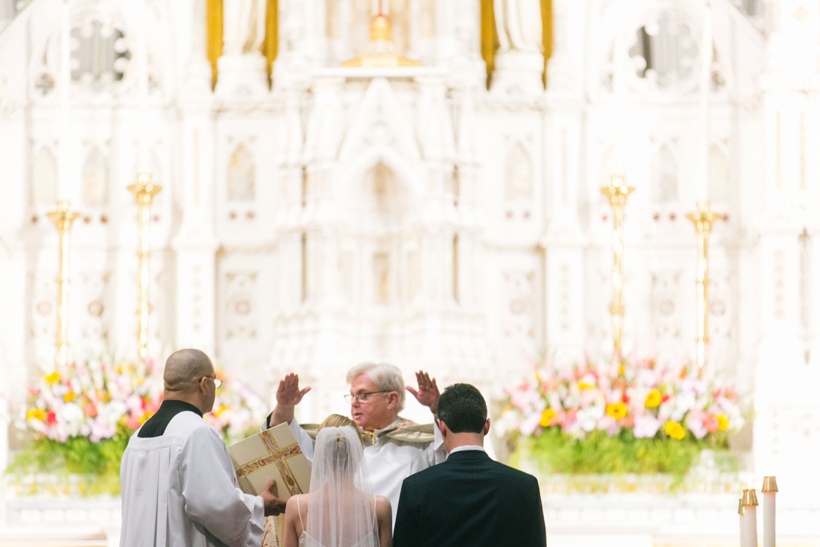 priest blessing the bride and groom at the altar during traditional Roman Catholic wedding ceremony
