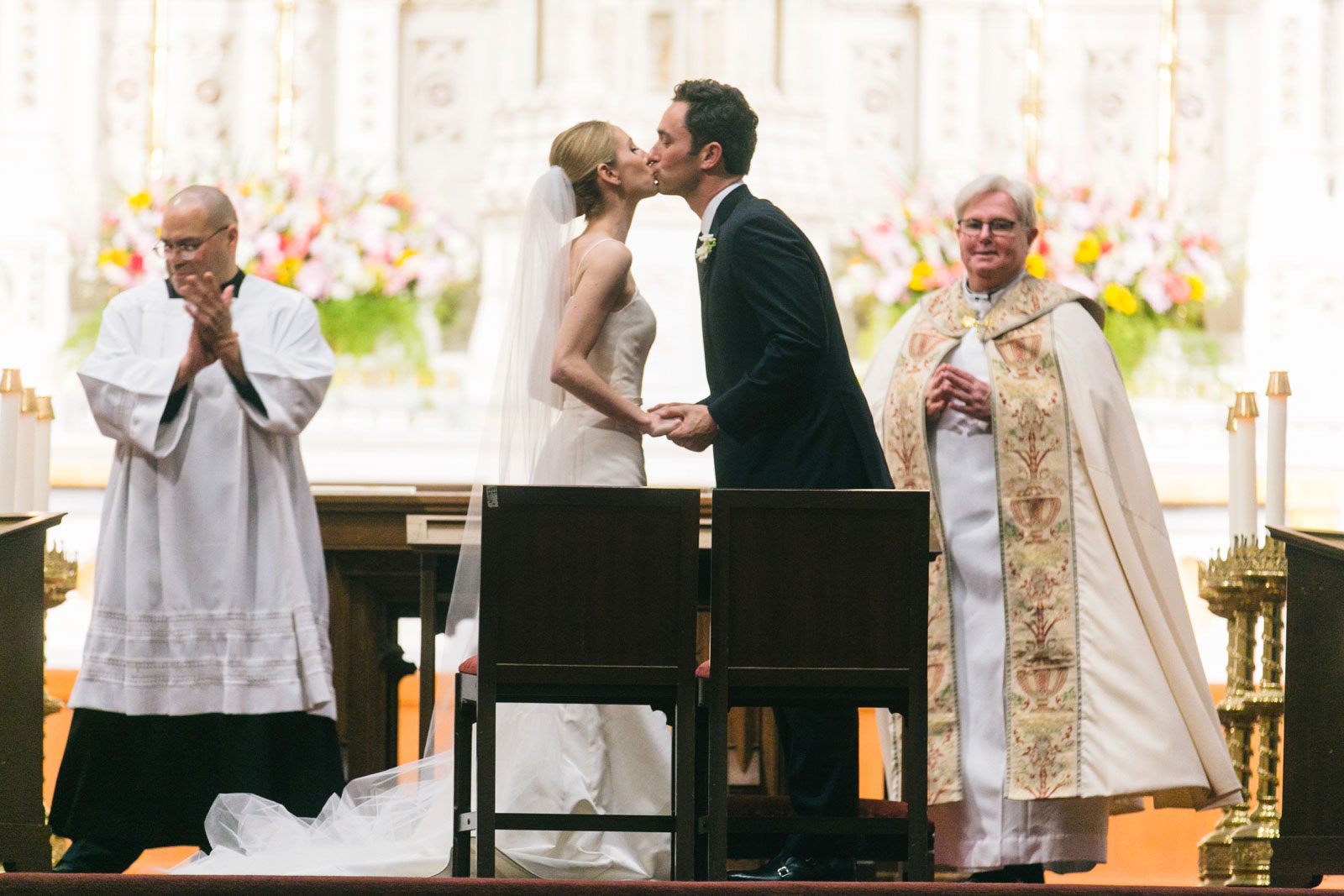 bride and groom share their first kiss at wedding ceremony at Cathedral of the holy cross