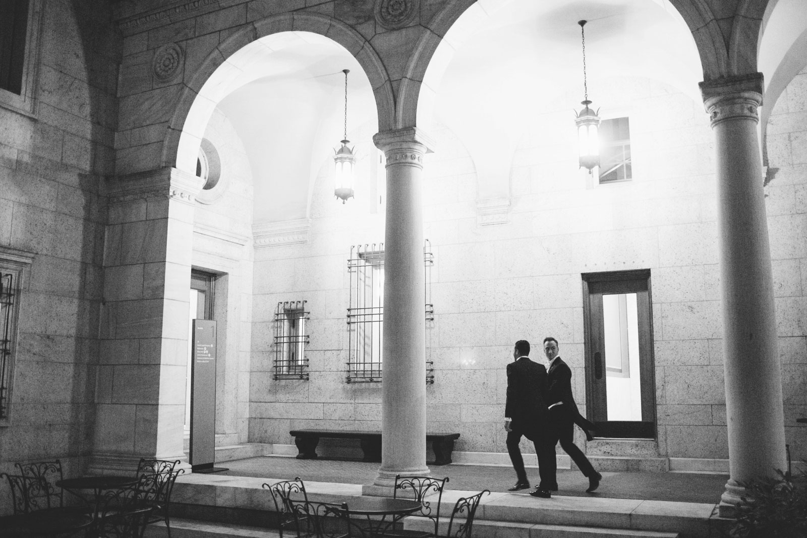 Grooms walking through courtyard after their same-sex wedding ceremony at Boston public library