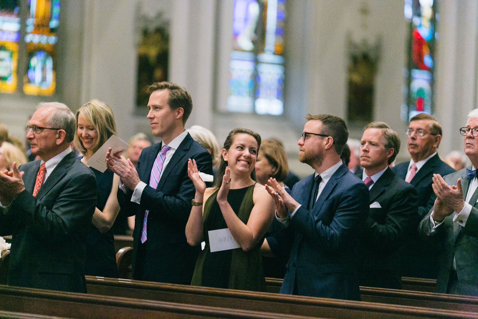 wedding guests clap and cheer as bride and groom share their first kiss at church wedding in boston