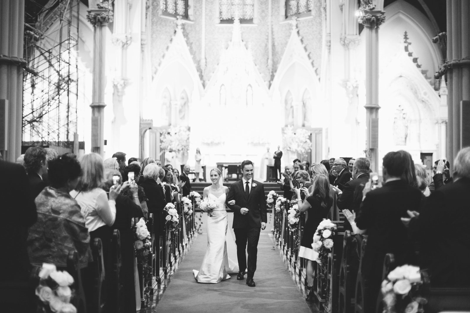 black and white shot of bride and groom smiling at guests as they walk back down the aisle
