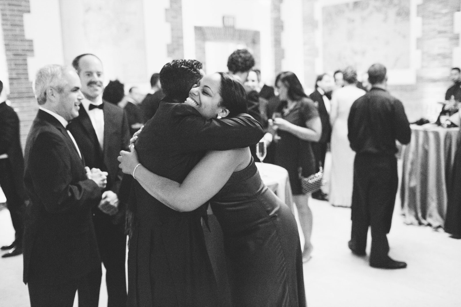 Black and white candid shot of groom hugging wedding guest a cocktail hour at Boston Public Library
