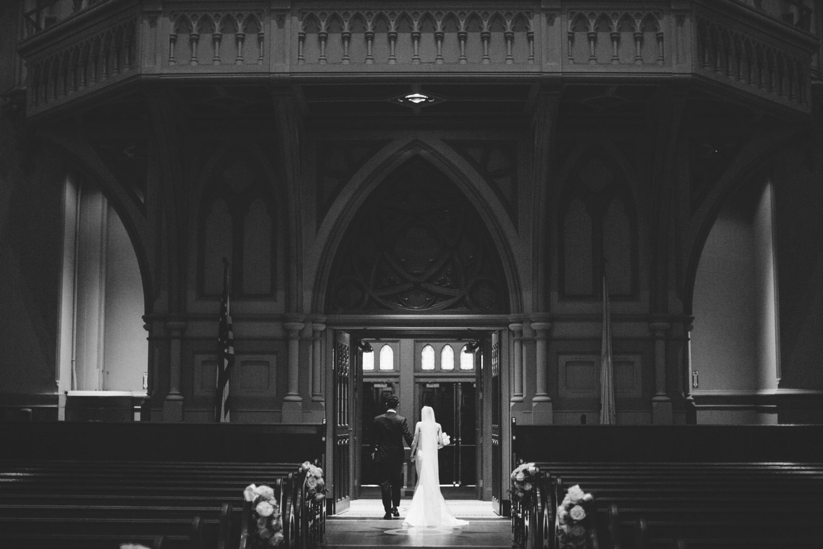 black and white shot from behind of bride and groom exiting historic Cathedral of the Holy Cross