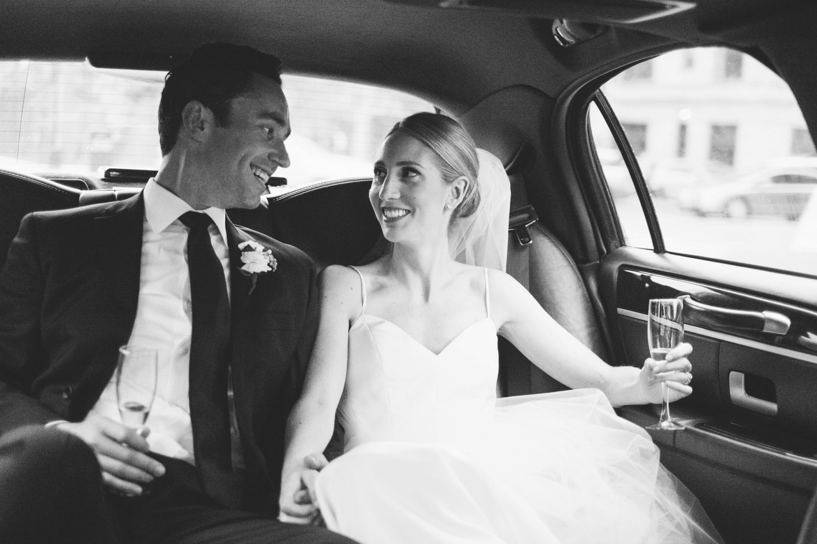 black and white shot of bride and groom sharing a moment in back of limo with champagne post-wedding