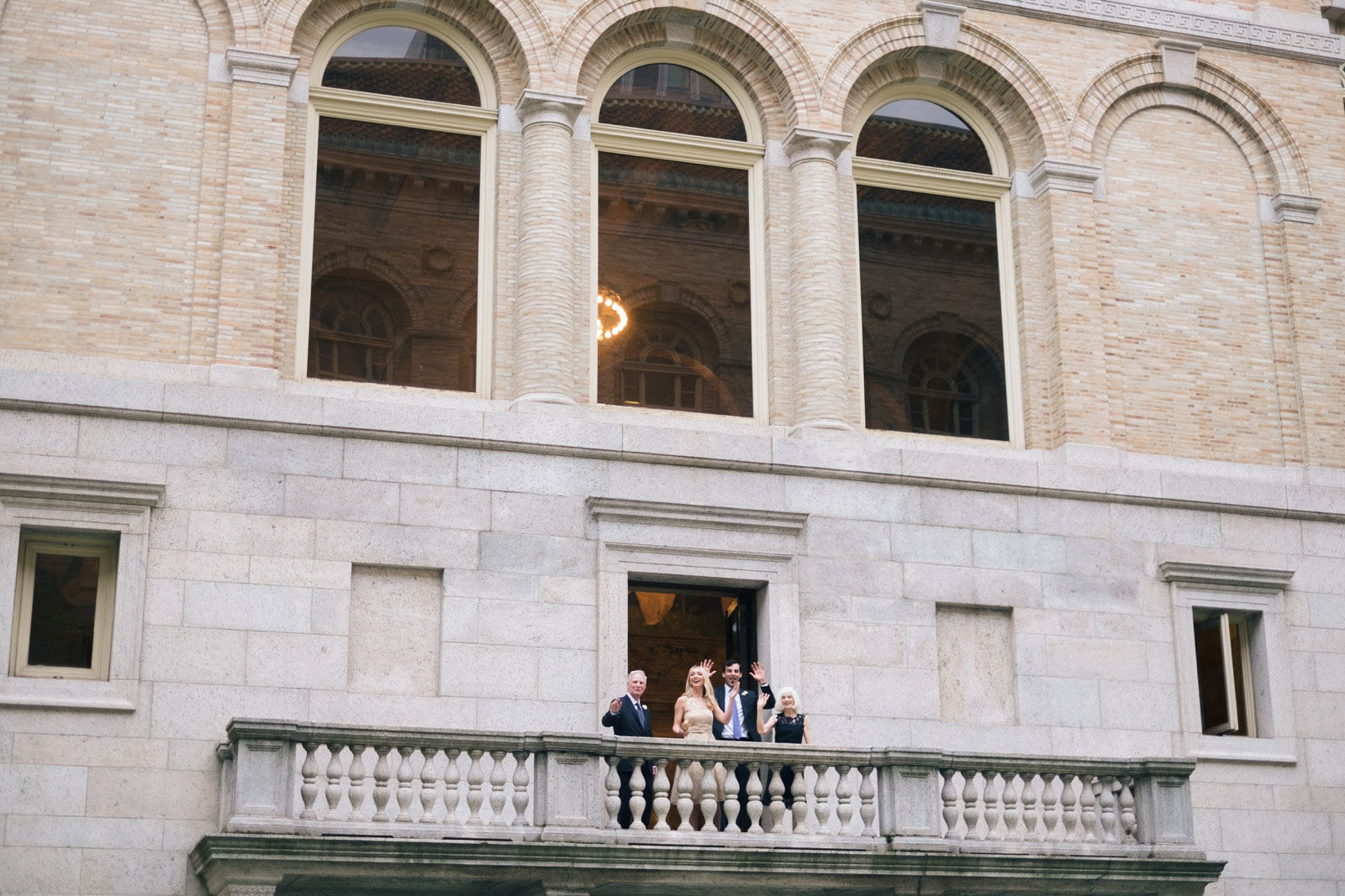 Wedding guests watch and cheer from balcony during formal portrait session at Boston Public Library