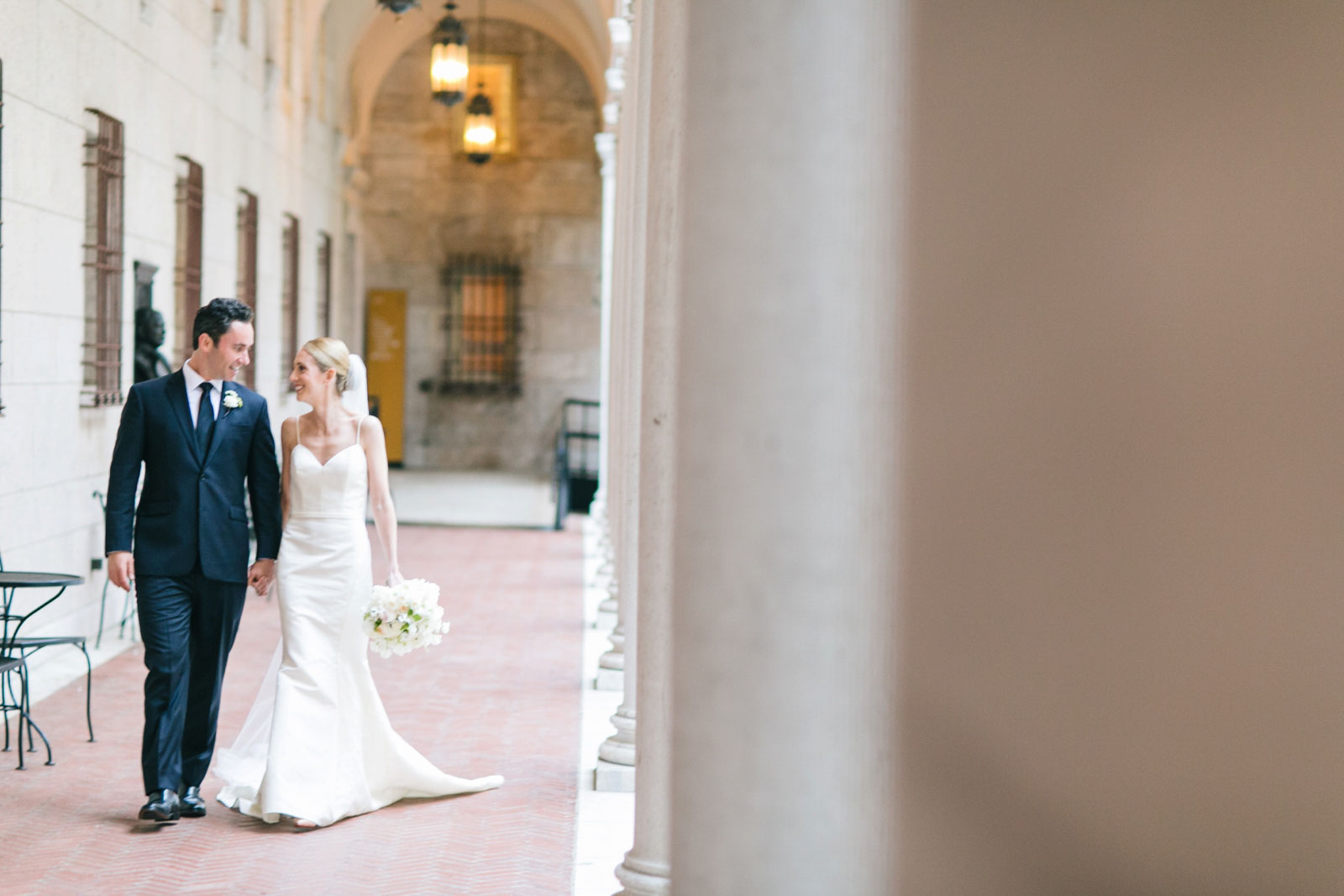 wedding portraits walking around courtyard of Boston public library with stone architecture