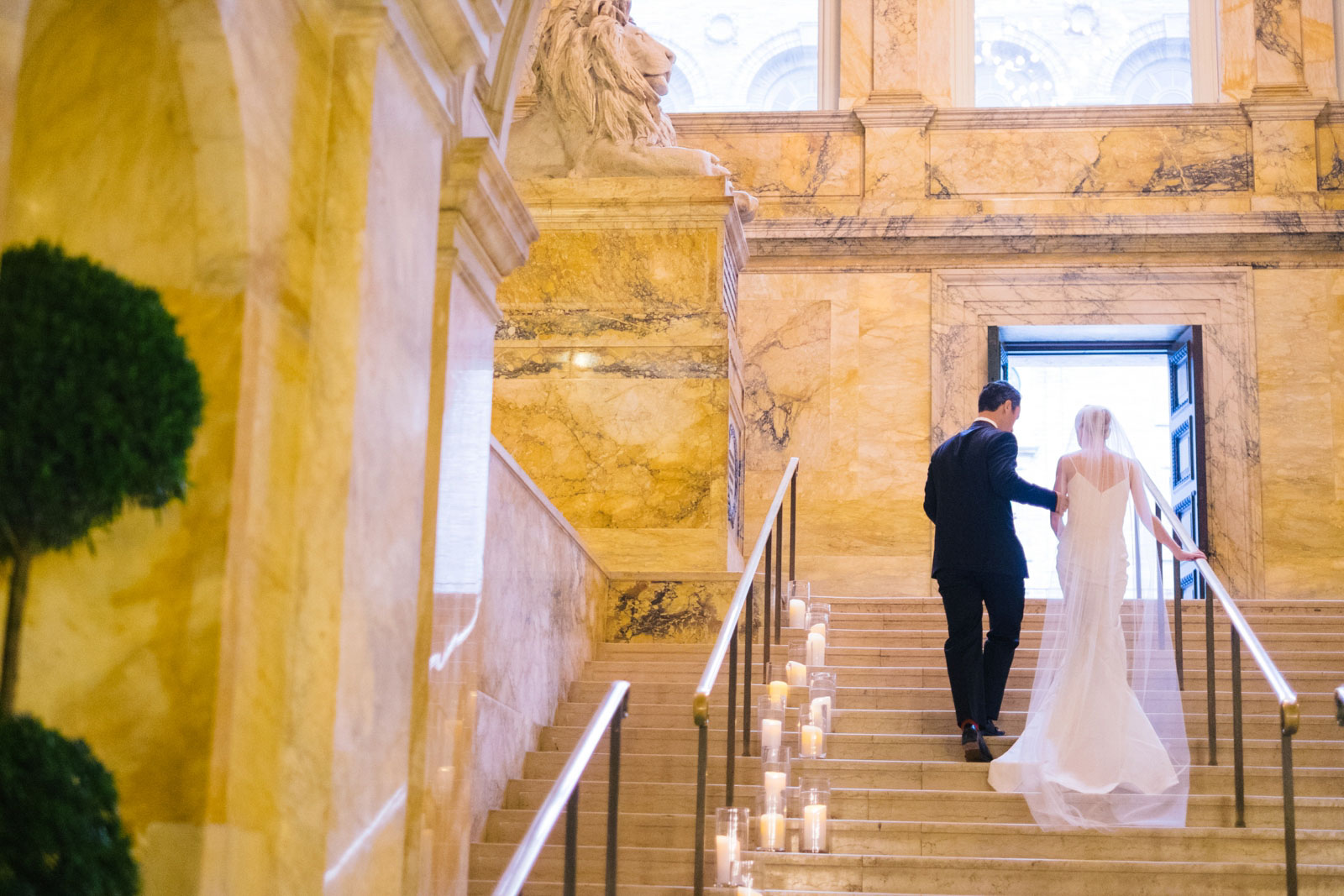 wedding portrait walking up stairs of quintessential marble staircase at Boston Public Library
