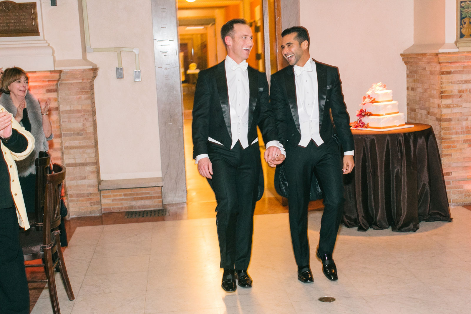 Couple enters their reception at the Boston public library holding hands, same-sex wedding