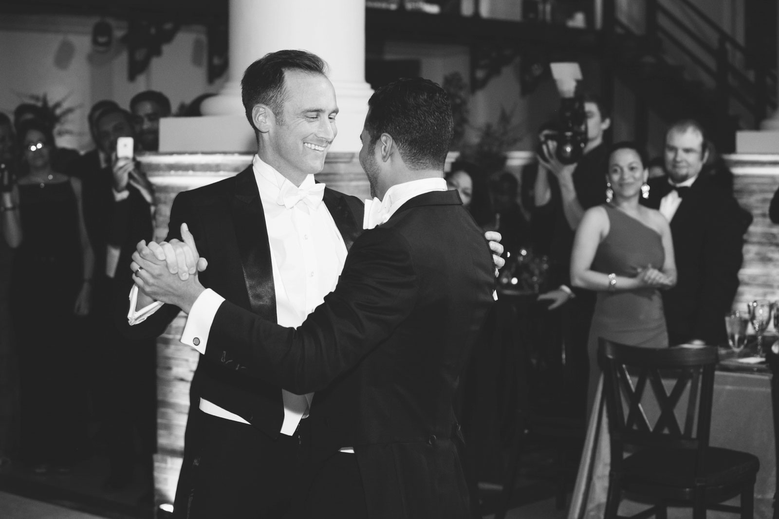 Black and white shot of grooms sharing romantic first dance at their Boston public library reception